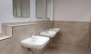 Frauenbad mit separaten Duschkabinen und Waschbecken